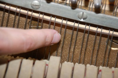 A finger tracing a piano string