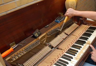 Person seated at the piano, using a tuning lever and an electronic tuner